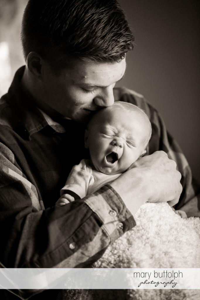 Man kisses his yawning baby at Skaneateles Newborn