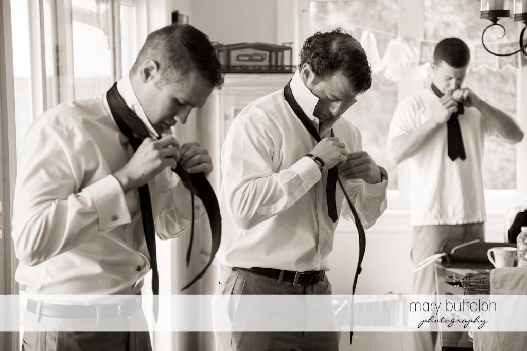 Groomsmen put on their neckties at Skaneateles Country Club Wedding