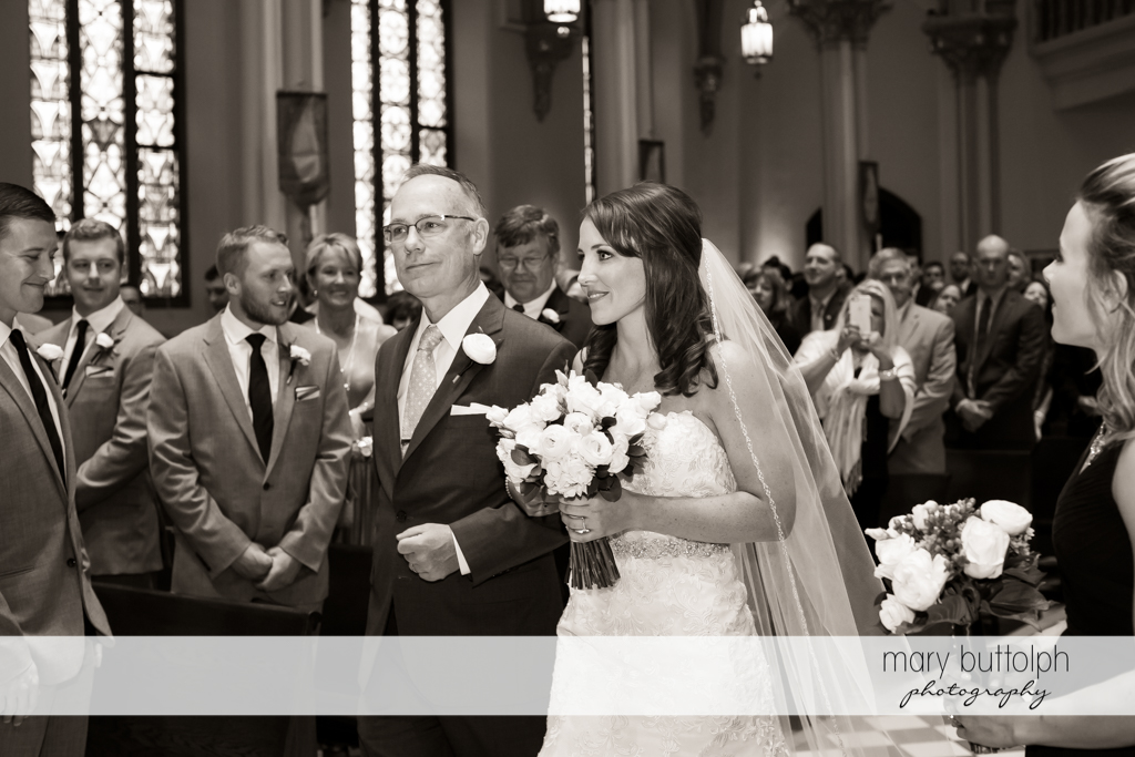 Bride and her father walk down the church aisle as guests look on at Skaneateles Country Club Wedding
