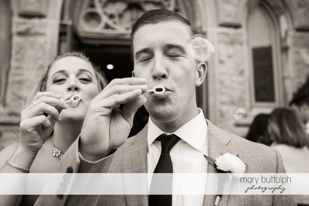 Guests blow bubbles for the couple outside the church at Skaneateles Country Club Wedding