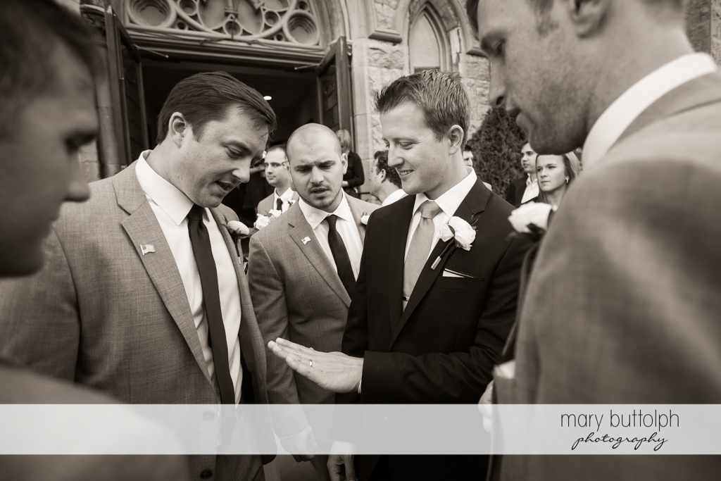 Groom shows his wedding ring to friends at Skaneateles Country Club Wedding
