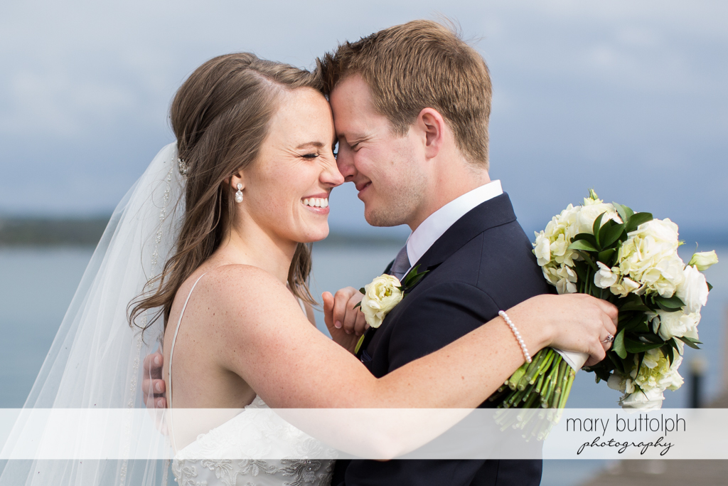 Couple rub noses in front of the lake at Skaneateles Country Club Wedding