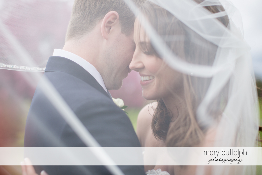 Couple are covered by the bride's wedding veil at Skaneateles Country Club Wedding