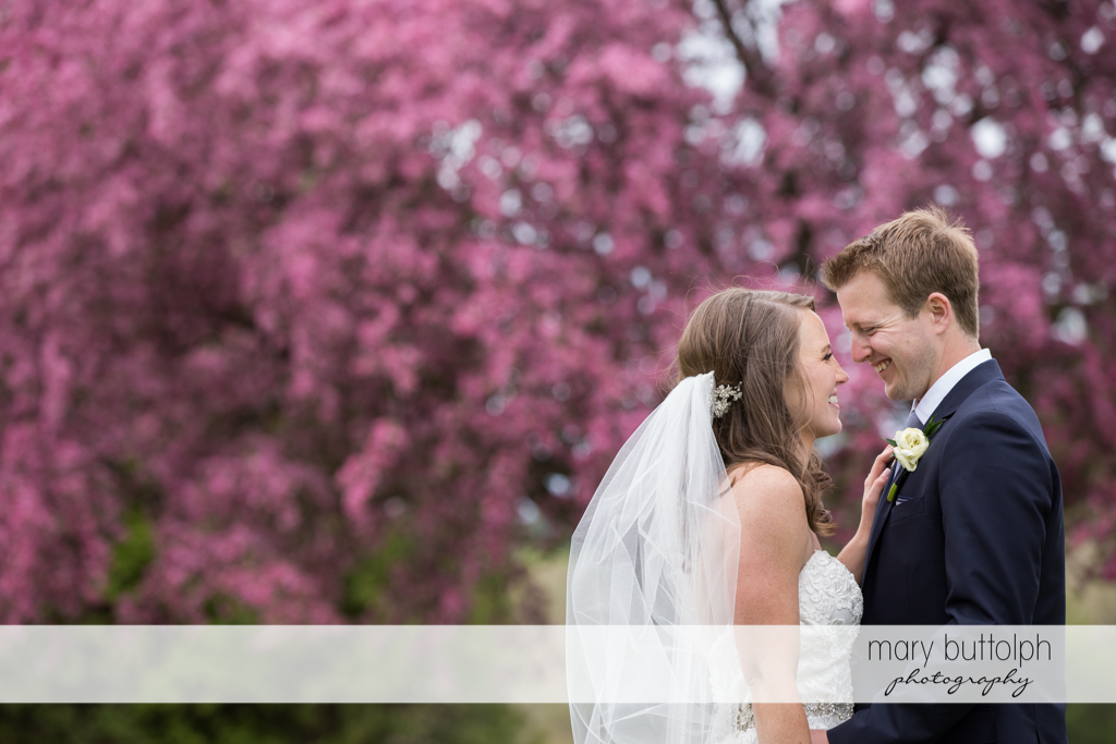 Couple share a happy moment near a tree with purple flowers at Skaneateles Country Club Wedding
