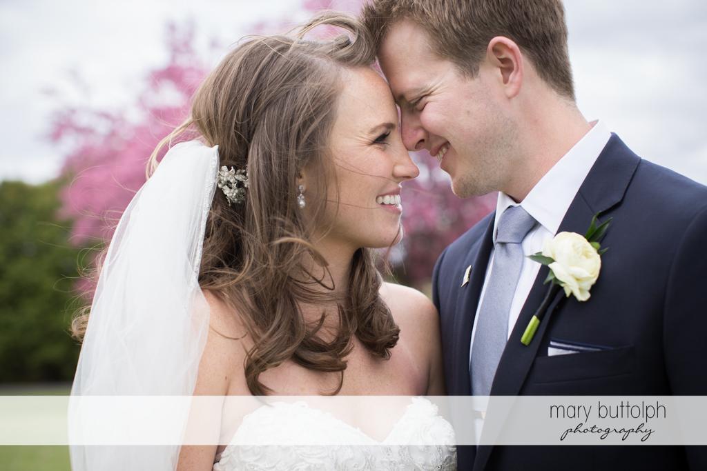 Couple show their affection in the garden at Skaneateles Country Club Wedding