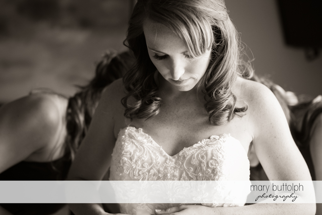 Bride waits as her wedding dress is adjusted by friends at Skaneateles Country Club Wedding