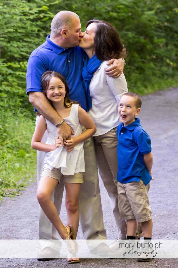 Couple kiss with kids on the road at Skaneateles Engagement