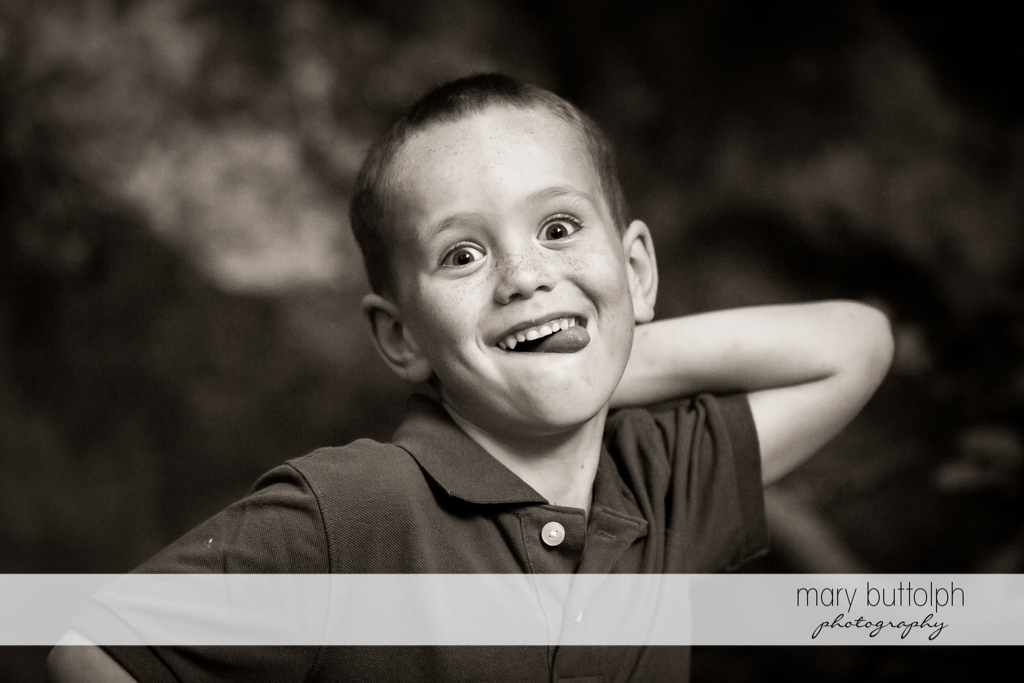 Couple's son makes a funny face while playing in the park at Skaneateles Engagement