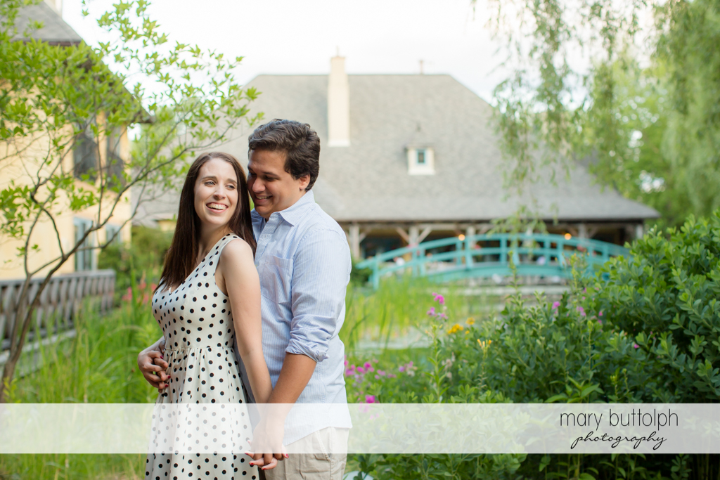 Couple pose before a big house at Skaneateles Engagement