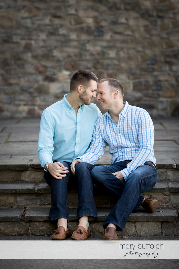 Same sex couple get intimate in front of a brick wall at Skaneateles Engagement