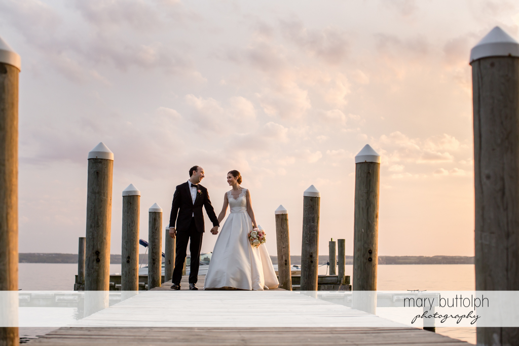 Couple stroll on the dock at the Inns of Aurora Wedding
