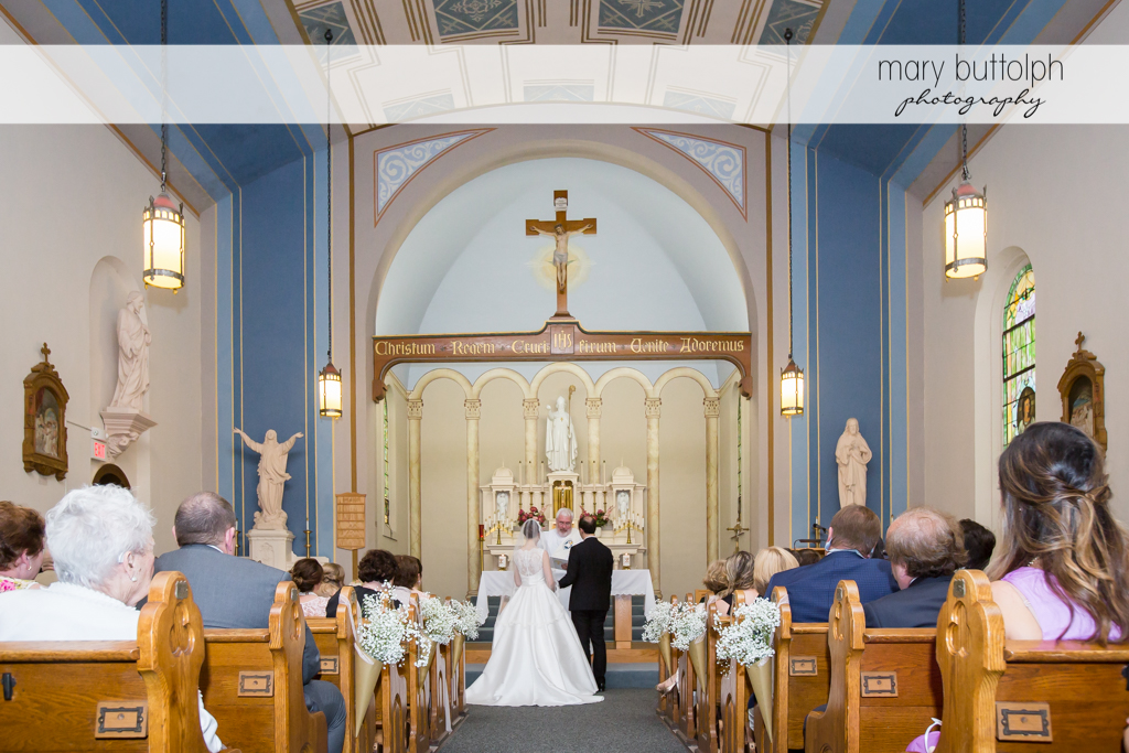 Couple face the priest in front of the altar at the Inns of Aurora Wedding
