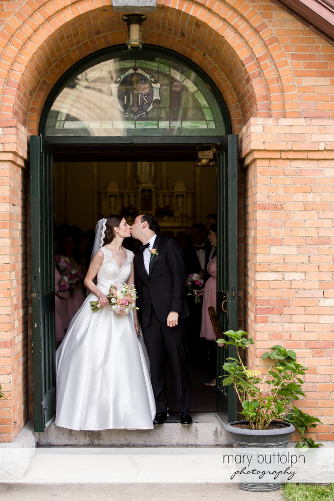 Couple kiss before they leave the church at the Inns of Aurora Wedding