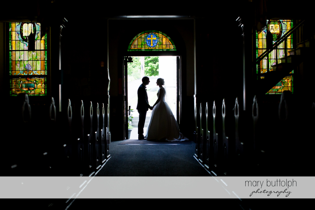 Couple stand on the church doorway at the Inns of Aurora Wedding