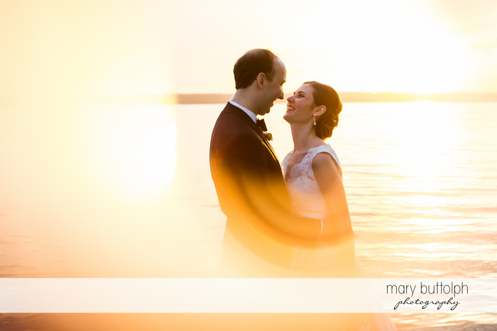 Couple catch the sun's rays near the lake at the Inns of Aurora Wedding