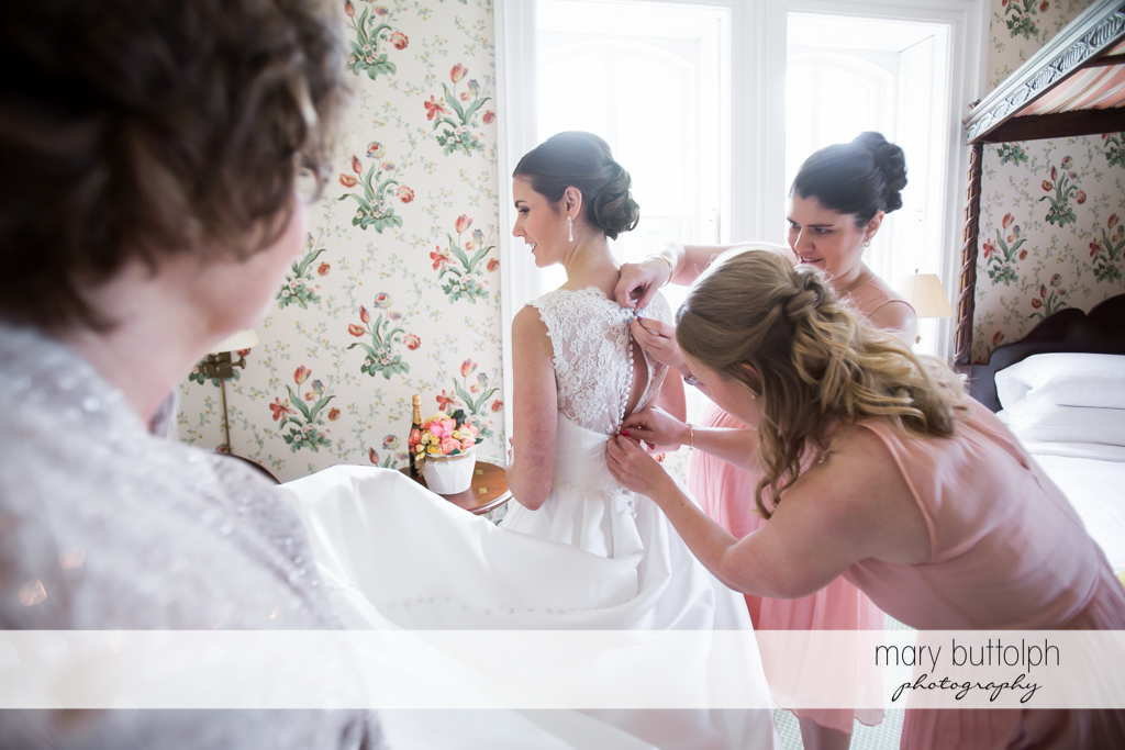 Brides get a little help from her bridesmaids who fix her dress at the Inns of Aurora Wedding