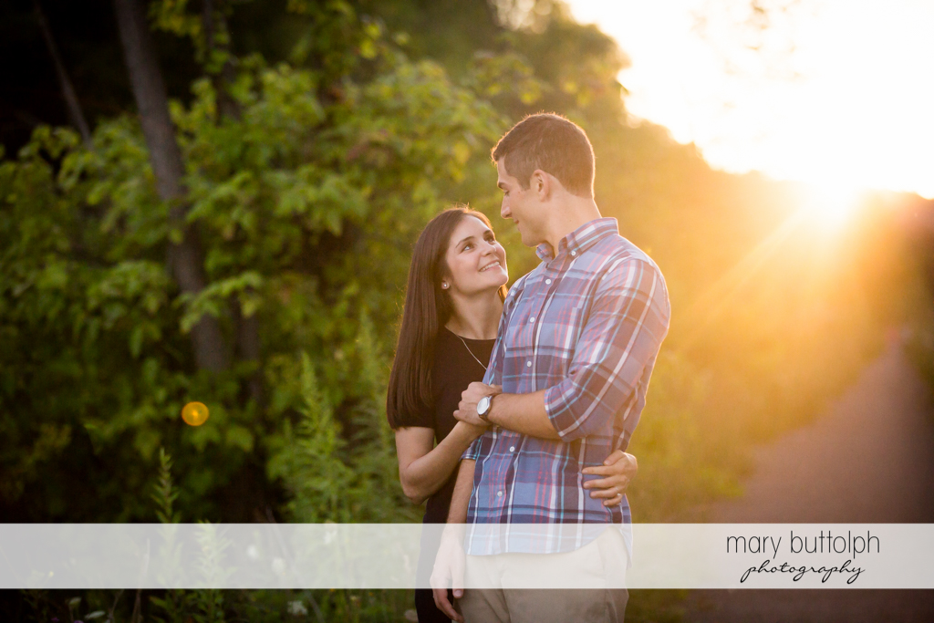 Couple walk in the park with the sun behind them at Finger Lakes Engagement