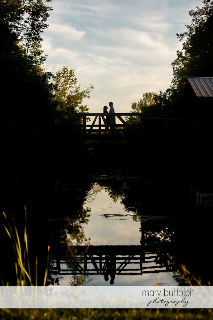 Couple's reflection appears on the lake as the two pause at the middle of a bridge at Finger Lakes Engagement