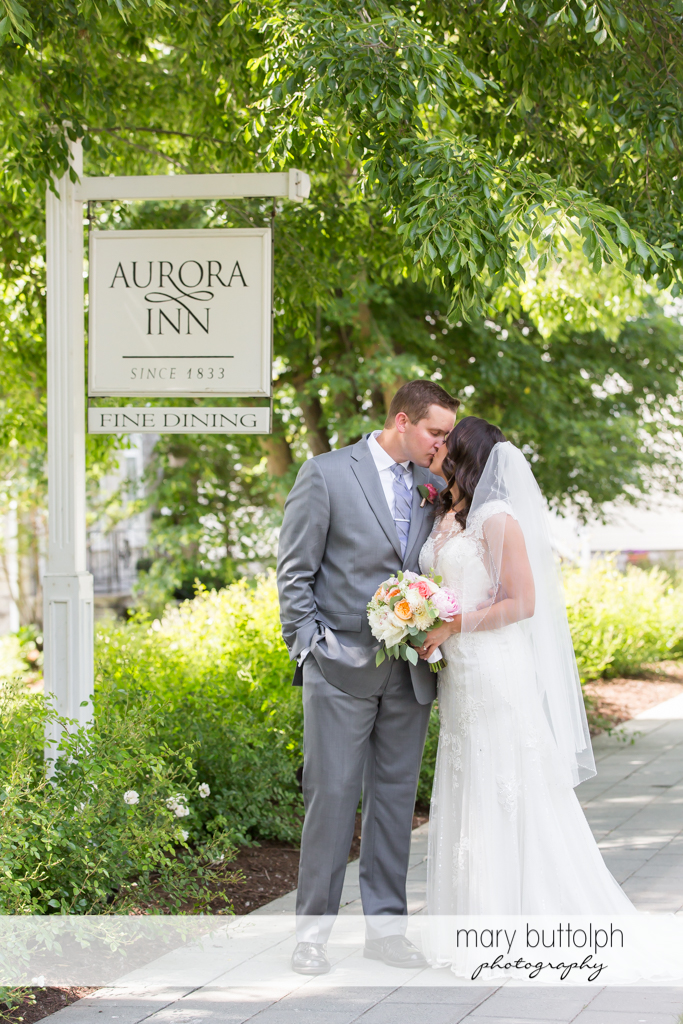 Couple kiss in front of an old sign at the Inns of Aurora Wedding