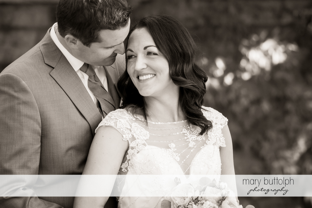 Couple share a tender moment in the garden at the Inns of Aurora Wedding