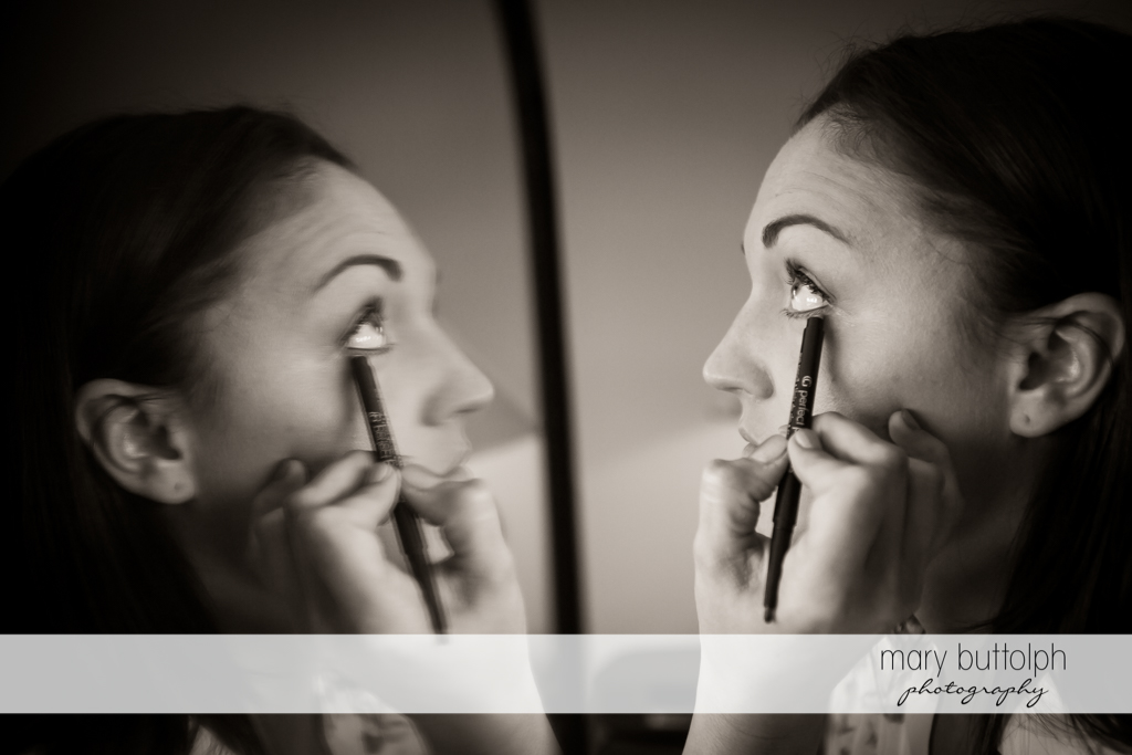 Bride puts eye makeup to enhance her looks at the Inns of Aurora Wedding