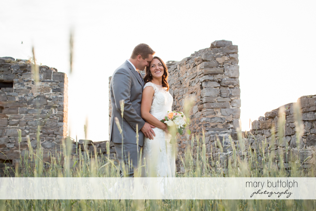 Couple pose in front of stone structures at the Inns of Aurora Wedding
