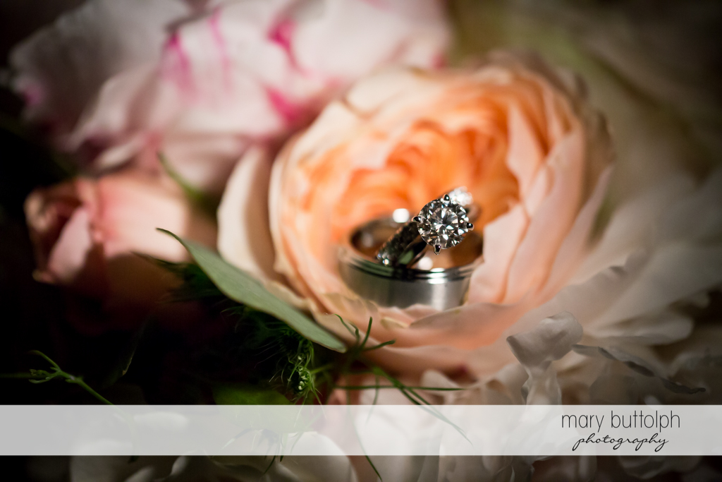 Bride's wedding ring rests on a flower at the Inns of Aurora Wedding