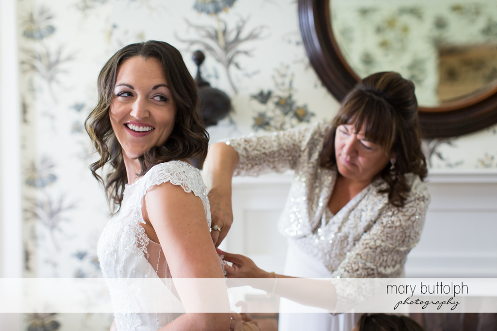 Bride gets a little help from her mother in putting on her wedding dress at the Inns of Aurora Wedding