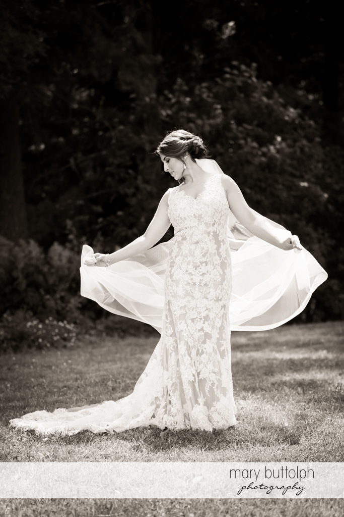 Bride shows her wedding gown in the garden at The Lodge at Welch Allyn Wedding