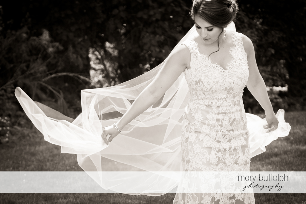 Bride's flowing wedding gown comes to life in the garden at The Lodge at Welch Allyn Wedding