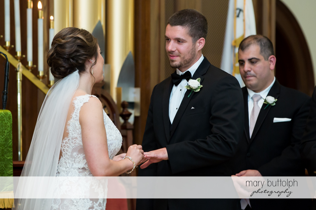 Bride puts the wedding ring on the groom's finger at The Lodge at Welch Allyn Wedding