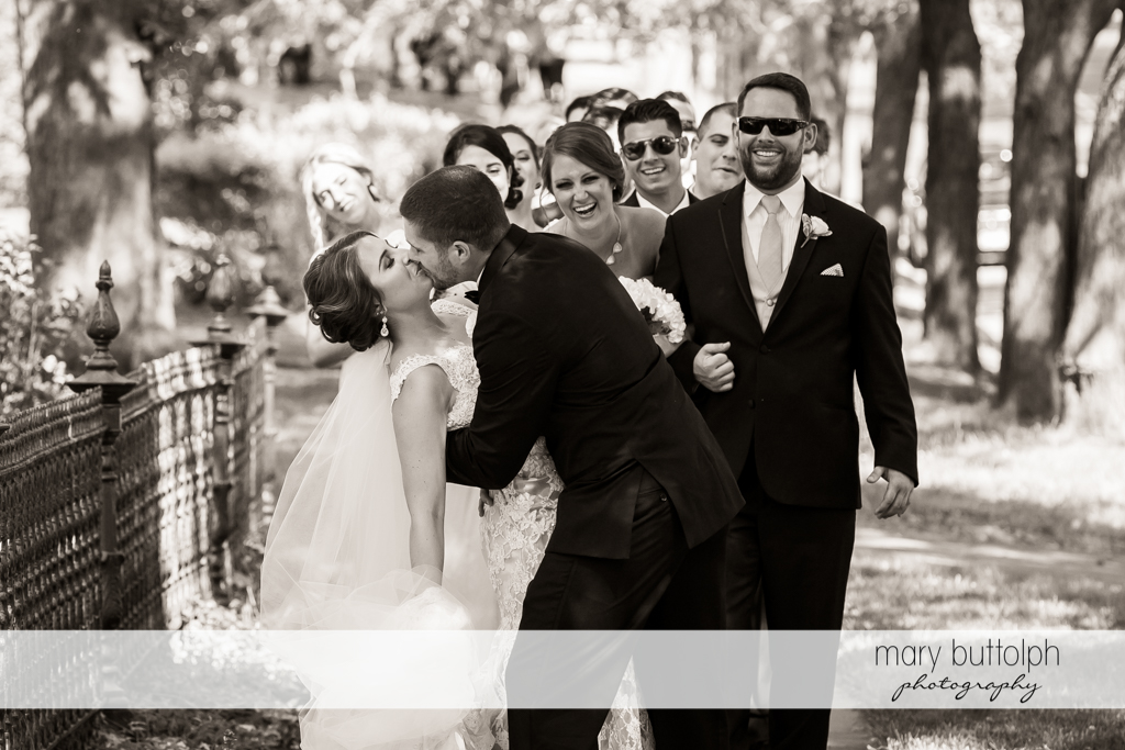 Couple kiss in front of the bridesmaids and groomsmen at The Lodge at Welch Allyn Wedding