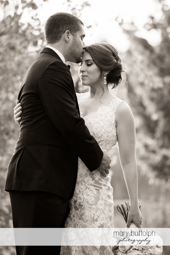 Groom plants a kiss on the bride's forehead at The Lodge at Welch Allyn Wedding