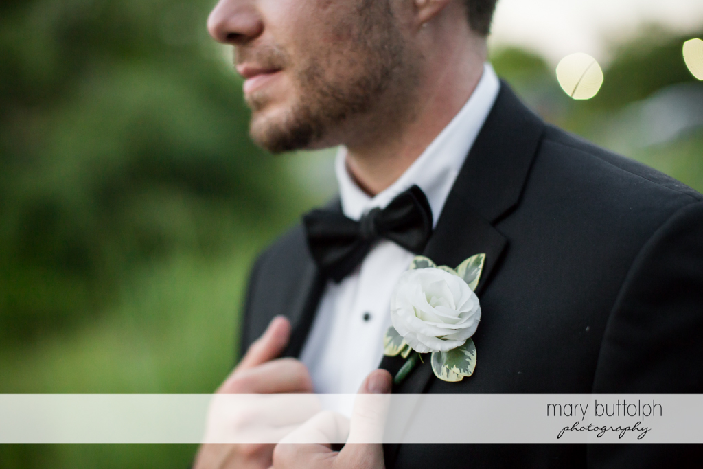 Groom's white boutonniere stands out on his dark coat at The Lodge at Welch Allyn Wedding