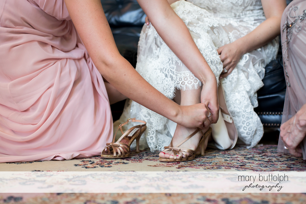 Bridesmaid helps put on the bride's shoes at The Lodge at Welch Allyn Wedding