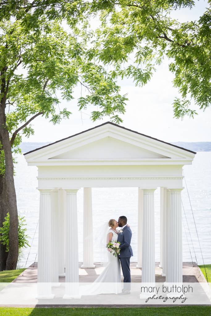 Couple kiss in the gazebo at the Inns of Aurora Wedding