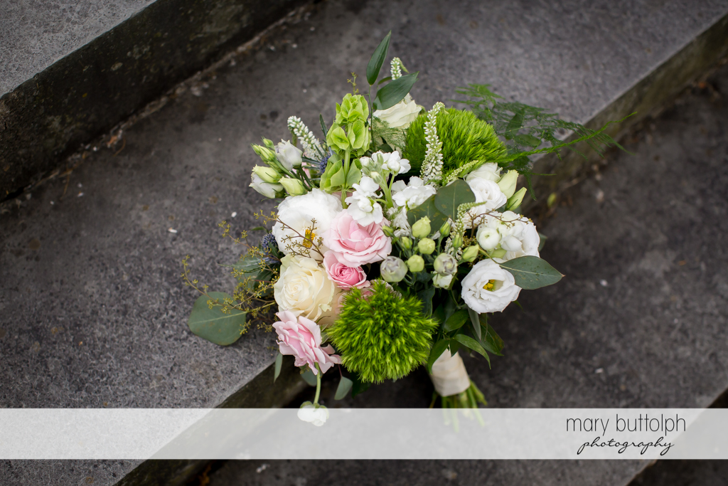 A bouquet on the concrete steps at the Inns of Aurora Wedding