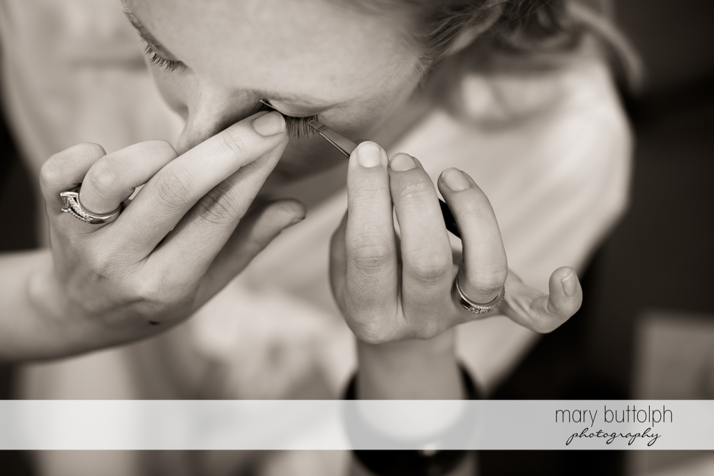 Bride fixes her eyelashes at the Inns of Aurora Wedding