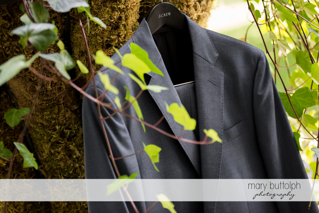 Groom's coat hangs from a tree in the garden at the Inns of Aurora Wedding