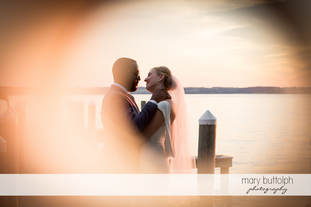 Couple embrace near the lake at the Inns of Aurora Wedding