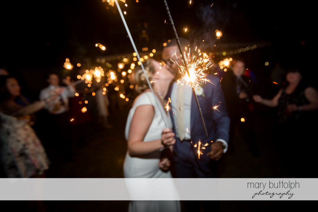 Couple kiss while holding sparklers at the Inns of Aurora Wedding
