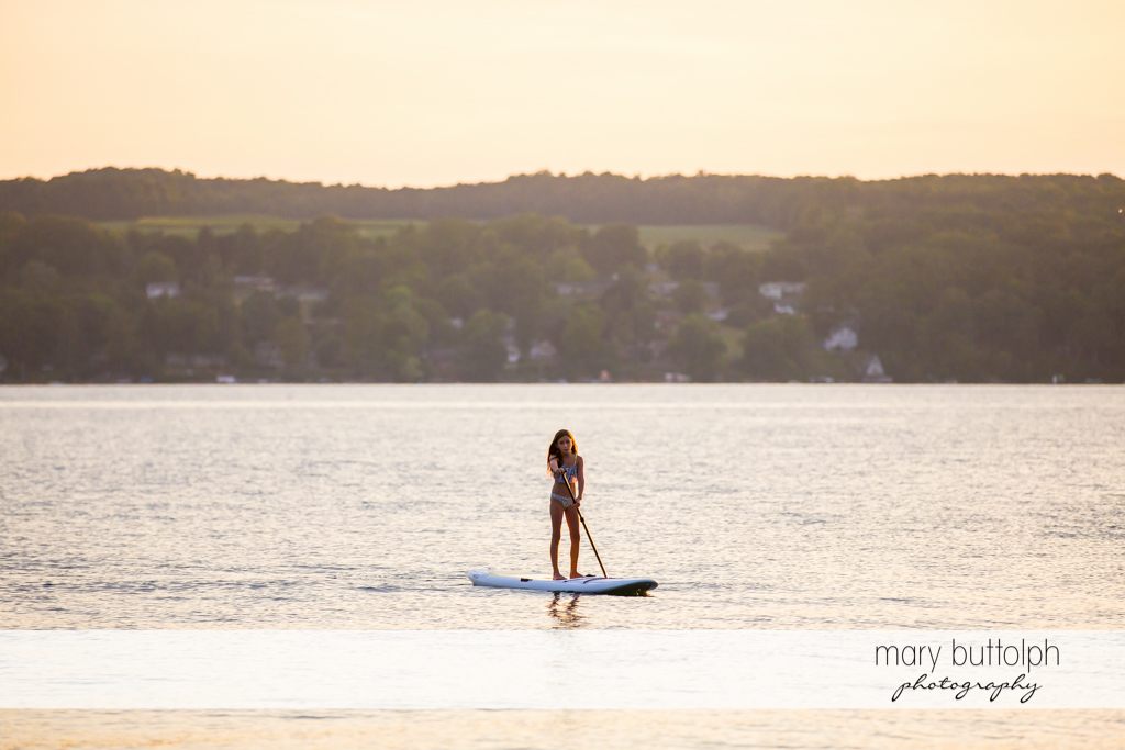 Girl uses her surfboard to cross the lake at Skaneateles Lake Vacation