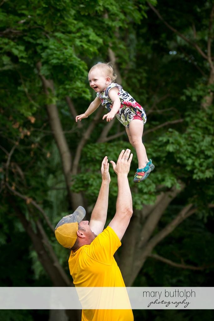 Man throws girl up in the air at Skaneateles Lake Vacation