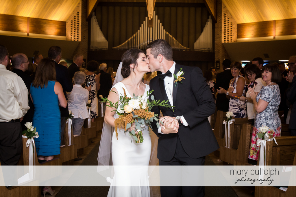 Couple kiss as they are applauded by guests at Genesee Grande Hotel Wedding