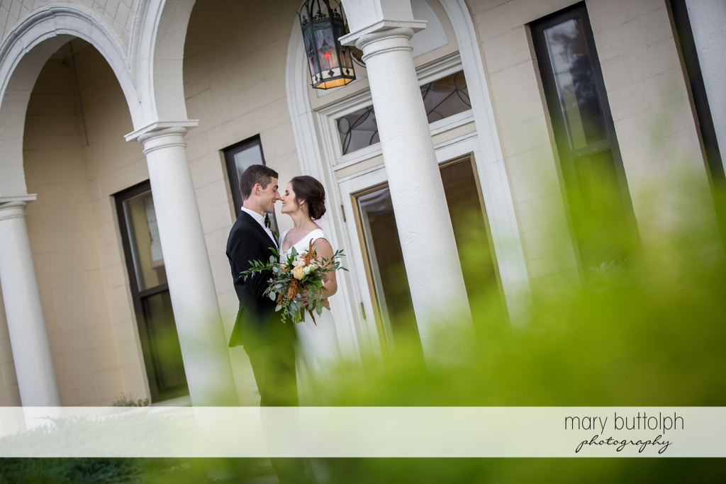 Couple rub noses in front of the building at Genesee Grande Hotel Wedding