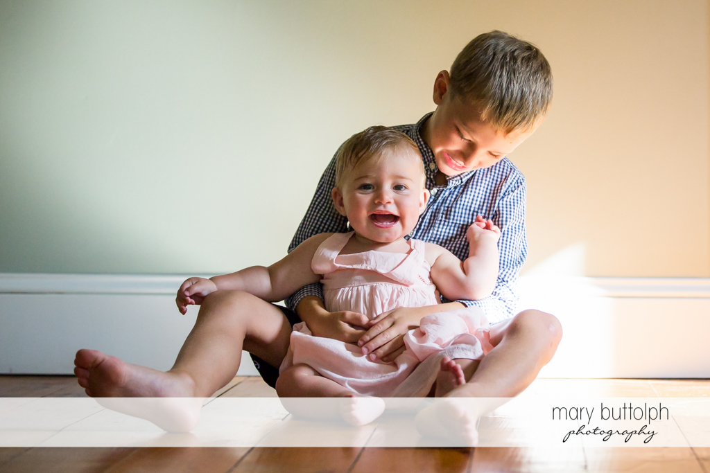 Boy and his younger sister play on the floor at Skaneateles