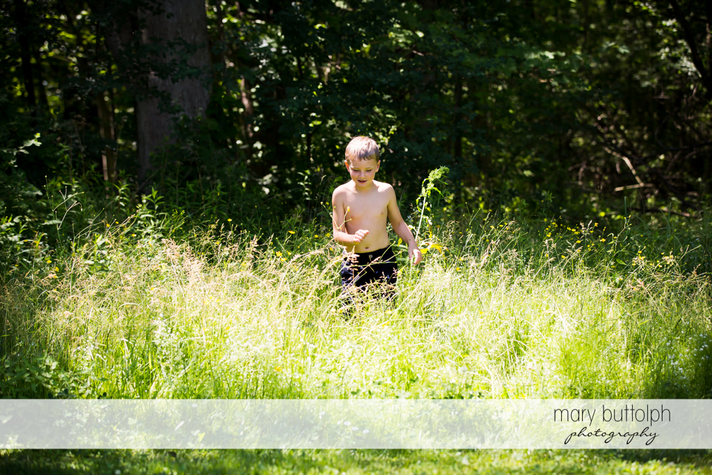 Boy plays in front of trees in the garden at Skaneateles