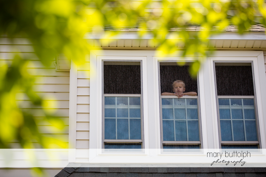 Boy watches from the window of his home at Skaneateles