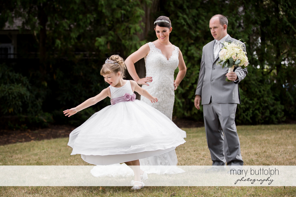 Bride's daughter plays in the garden as the couple look on at The Sherwood Inn Wedding