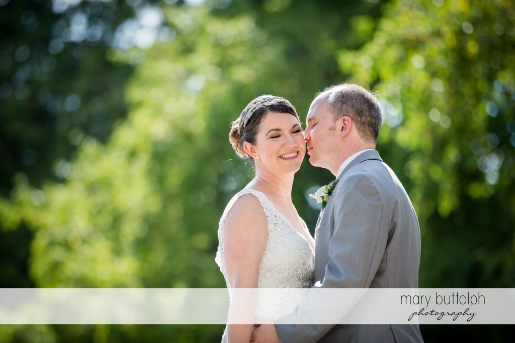 Couple share a tender moment in the park at The Sherwood Inn Wedding
